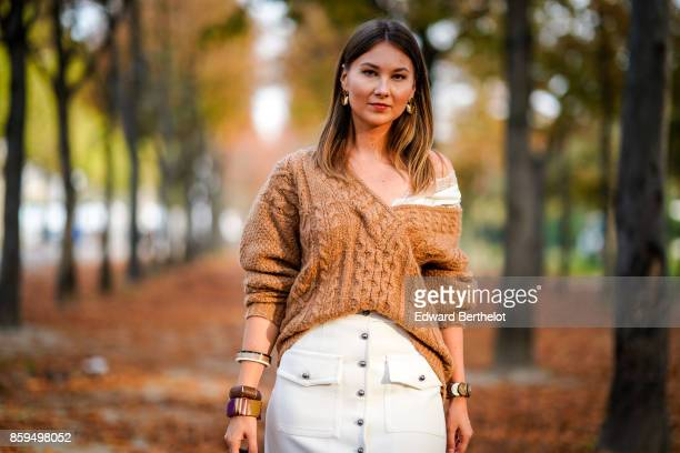 Angelica Ardasheva wears a camel Vneck pullover and a white skirt outside the Rochas show during Paris Fashion Week Womenswear Spring/Summer 2018 on...