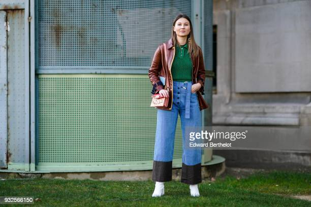 Angelica Ardasheva wears a green knit top a camellined brown leather jacket with black and blue inserts waisted blue denim buttonfront and sliding...