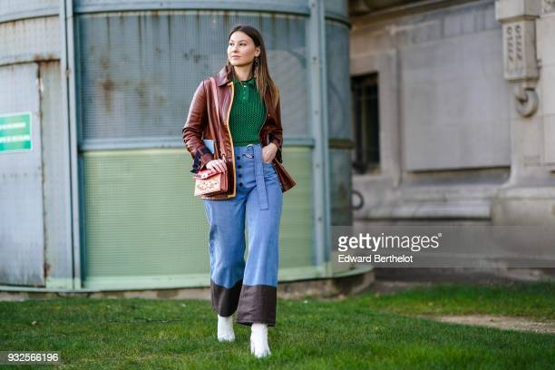 Angelica Ardasheva wears a green knit top a camellined brown leather jacket waisted blue denim buttonfront and sliding buckle belt wideleg pants with...