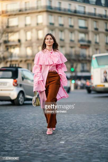 Angelica Ardasheva wears a pink ruffled long shirt a bag with embroidery brown flared pants pink shoes outside Rochas during Paris Fashion Week...