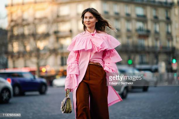 Angelica Ardasheva wears a pink ruffled long shirt, a bag with embroidery, brown flared pants, pink shoes, outside Rochas, during Paris Fashion Week...