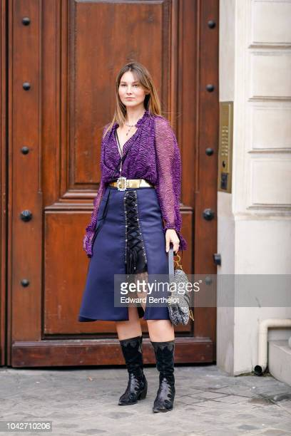 Angelica Ardasheva wears a purple shirt a blue skirt black boots a Dior Saddle bag outside Andrew GN during Paris Fashion Week Womenswear...