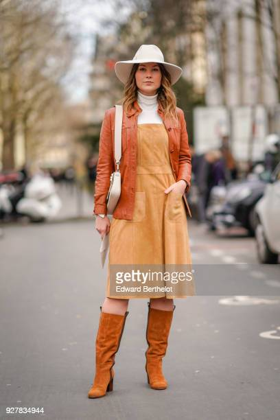 Angelica Ardasheva wears a white hat a brown leather jacket orange dress brown leather boots outside Giambattista Valli during Paris Fashion Week...