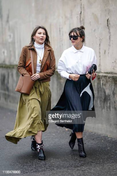 Angelica Ardasheva wears earrings a white turtleneck a brown bucket bag a brown leather jacket a lustrous almondgreen velvet ruffled and gathered...
