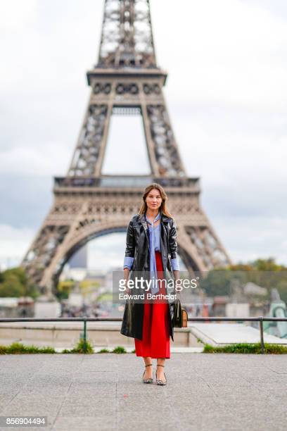 Angelica Ardasheva wears red pants a blue top a black coat outside Hermes during Paris Fashion Week Womenswear Spring/Summer 2018 on October 2 2017...