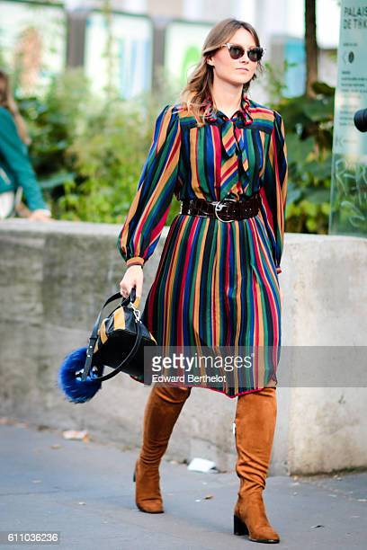 Angelika Ardasheva is wearing a multi colored striped dress sunglasses brown boots and a bag outside the Rochas show at the Palais de Tokyo during...