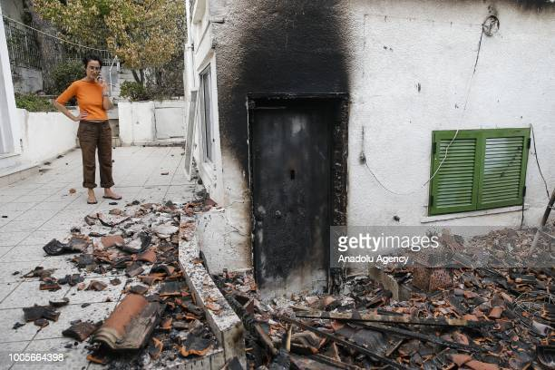 Angeliki Pollali a survivor of wildfires is seen at her damaged house during an interview after wildfires hit the village of Mati near in Athens...