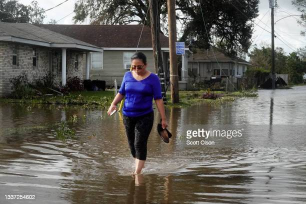Angelina Coxum walks down a street flooded by Hurricane Ida to check on a relatives home on August 30, 2021 in Kenner, Louisiana. Ida made landfall...