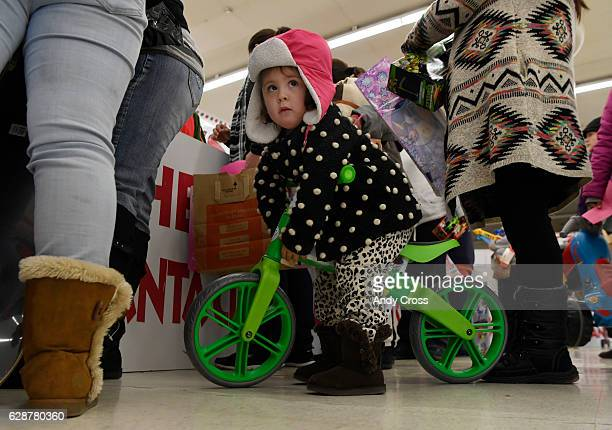 Angelina Estrada tries out her new push bike at the 86th annual Denver Santa Claus Shop at the old Kmart store near Evans Ave and Monaco St December...