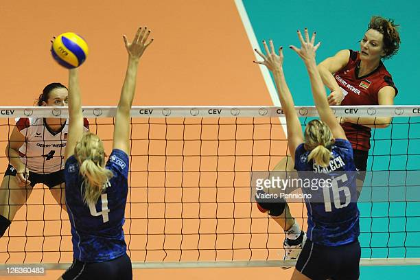 Angelina Grun of Germany smashes as Christina Bauer and Helene Schleck of France block during the women Volleyball European Championship match...