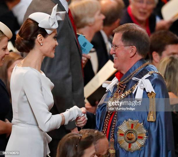 Angelina Jolie an Honorary Dame Commander of The Most Distinguished Order of Saint Michael and Saint George greets Lord George Robertson as she...