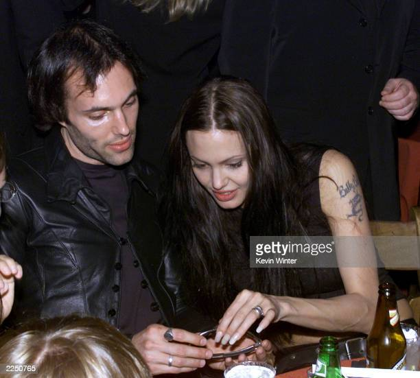 Angelina Jolie and her brother Jamie Haven Voight check out his sunglassses at the afterparty for the premiere of the film 'Lara Croft Tomb Raider'...