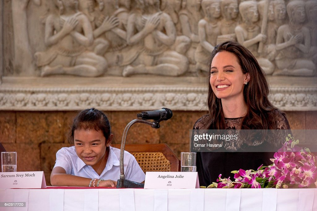 Angelina Jolie (right) laughs with actress Sareum Srey Moch (left) during a press conference ahead of the premiere of their new movie 'First They Killed My Father' set up at the Raffles Grand Hotel D'Angkor on February 18, 2017 in Siem Reap, Cambodia. Angelina Jolie is in Siem Reap for the world premiere of her new movie, 'First They Killed my Father,' a Netflix-produced adaption of the autobiography by the same name penned by Loung Ung, who lived through the Khmer Rouge regime as a young child. The film will be screened Saturday night in the Angkor Wat temple complex, and released later this year on Netflix.