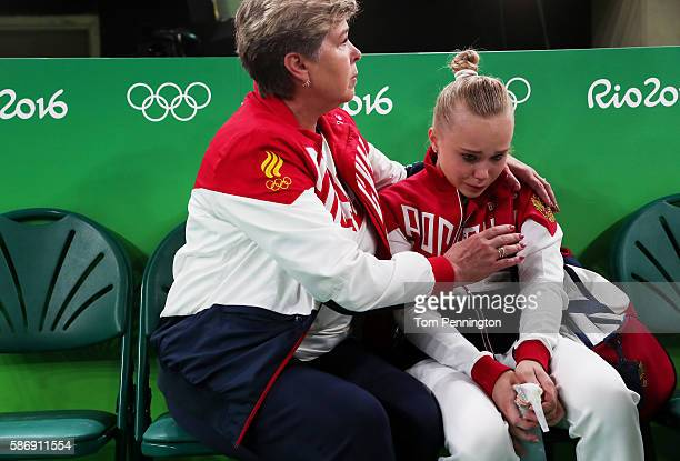Angelina Melnikova of Russia is consoled by a coach after not qualifying for the all around during Women's qualification for Artistic Gymnastics on...