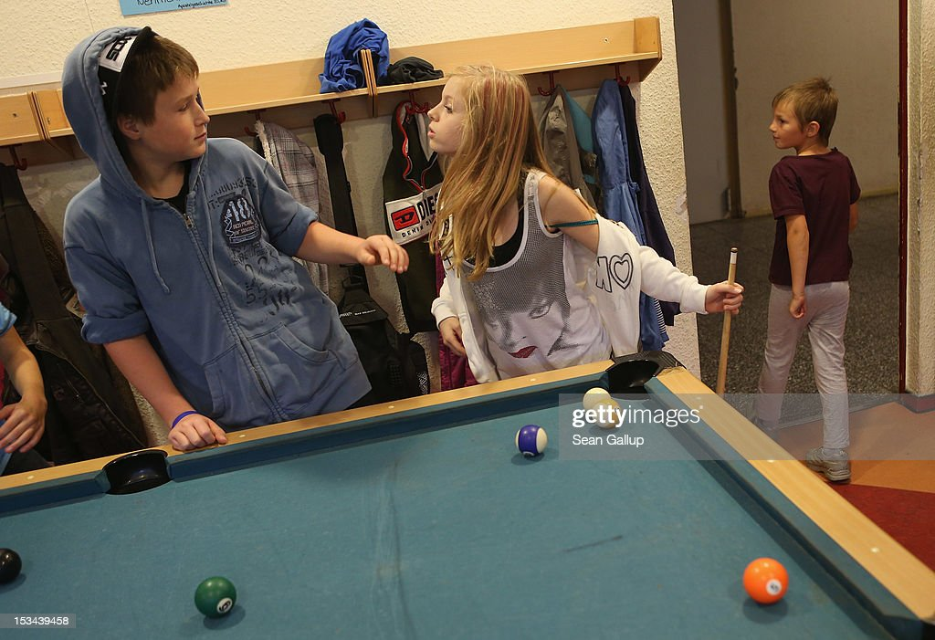 Angelina, 11, shows a boy who's boss while playing pool at the 'Arche' youth center in Marzahn-Hellersdorf district on October 5, 2012 in Berlin, Germany. The Arche (which means Ark) is a Christian-based facility that provides children of all ages with a hot lunch, help with homework, arts and play facilities and in general a welcome place to come to in Marzahn-Hellersdorf district in east Berlin, a district with high levels of unemployment and social problems. An employee said up to 90% of the children come from challenged families and that many arrive at Arche illiterate.