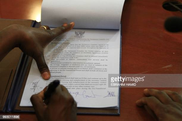 Angelina Teny chief negotiator of the rebel Machar group and the wife of rebel leader Riek Machar signs a security deal in the Sudanese capital...