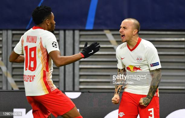 Angelino of RB Leipzig celebrates with teammate Christopher Nkunku after scoring their team's first goal during the UEFA Champions League Group H...