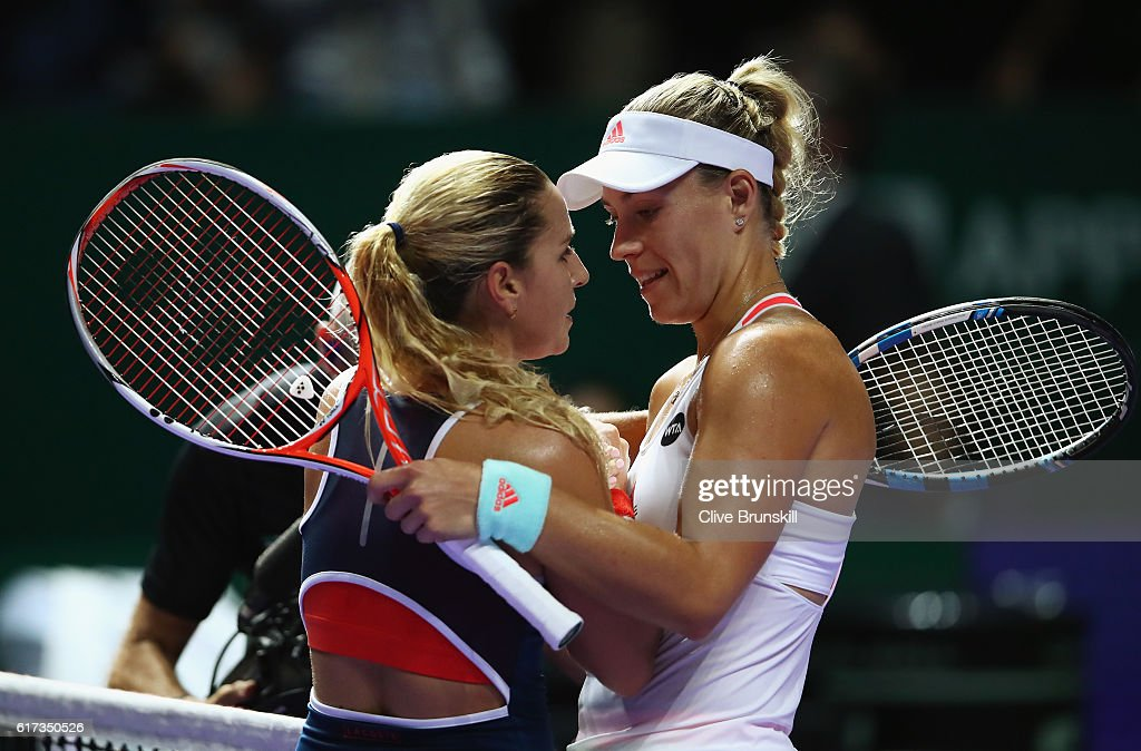 Angelique Kerber (R) of Germany celebrates victory in her singles match against Dominika Cibulkova of Slovakia during day 1 of the BNP Paribas WTA Finals Singapore at Singapore Sports Hub on October 23, 2016 in Singapore.
