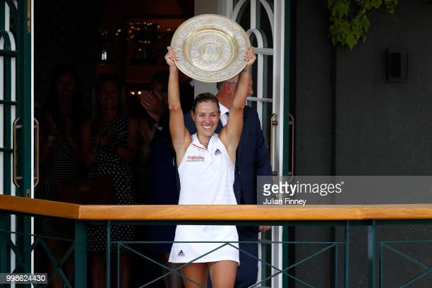 Angelique Kerber of Germany lifts the Venus Rosewater Dish on the balcony of Centre Court after defeating Serena Williams of The United States in the...