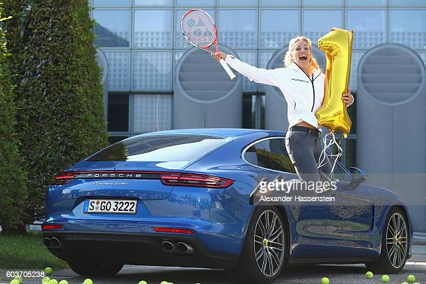 Angelique Kerber of Germany poses in front of a new Porsche Panamera Turbo after returning as new Tennis World number One and winner of the US Open...