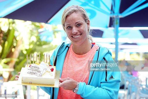 Angelique Kerber of Germany poses with a birthday cake which was presented to her by Australian Open Tournament Director Craig Tiley during day three...
