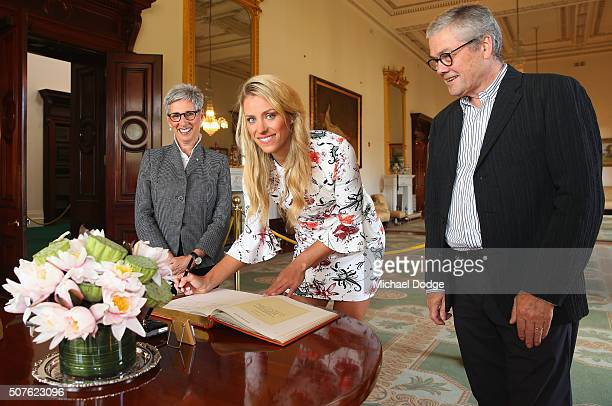 Angelique Kerber of Germany signs a book alongside Governor Of Victoria the Honourable Linda Dessau AM and her husband Judge Anthony Howard during a...