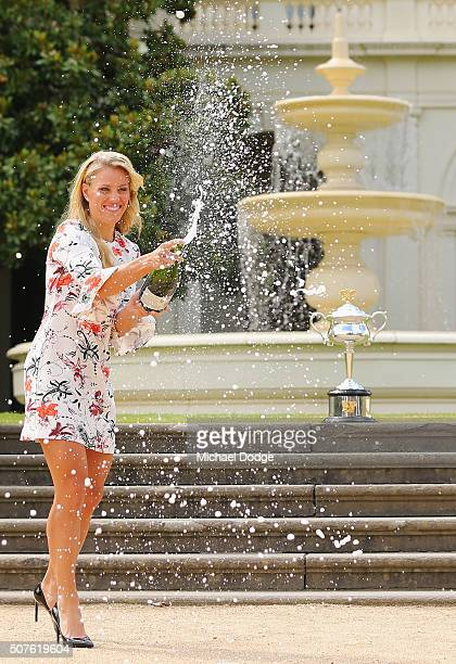 Angelique Kerber of Germany sprays champagne with the Daphne Akhurst Memorial Cup during a photocall at Government House after winning the 2016...