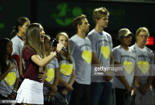 Angelique Menses of Marjory Stoneman Douglas High School sings the National Anthem with members of the boys and girls tennis team and the players...