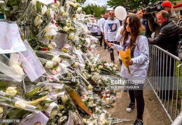 Angelique's sister and father lay flowers during a march in Wambrechies northern France on May 1 in tribute to Angelique a 13yearold girl who was...