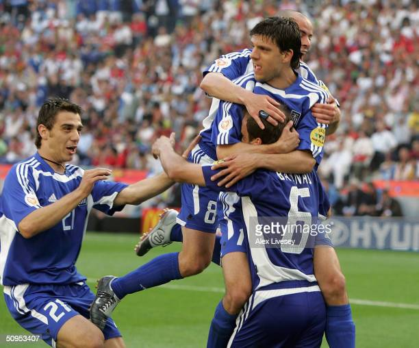 Angelis Basinas of Greece is mobbed after scoring the second goal with a penalty during the Portugal v Greece Group A opening match the 2004 UEFA...
