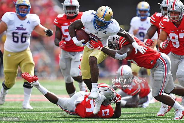 Angelo Brewer of the Tulsa Hurricane picks up yardage in the first quarter as Raekwon McMillan of the Ohio State Buckeyes moves in for the tackle at...