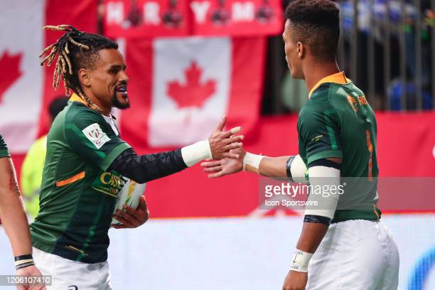 Angelo Davids of South Africa high fives teammate Selvyn Davids after scoring a try against the USA during their quarter-final match at the finals of...