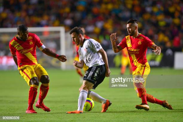 Angelo Enriquez of Atlas drives the ball against Gabriel Achilier of Morelia during the 10th round match between Monarcas and Atlas as part of the...