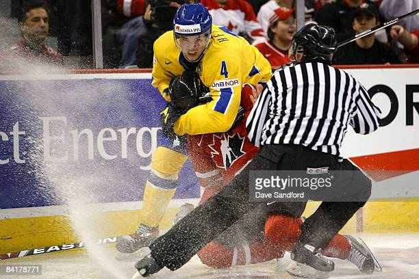 Angelo Esposito of Team Canada is jumped by Victor Hedman of Team Sweden during the 2009 IIHF World Junior Championships held at Scotiabank Place on...
