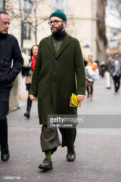 Angelo Flaccavento, wearing a grey printed sweater, long green coat, green pants, green shoes and green hat, is seen in the streets of Paris before...