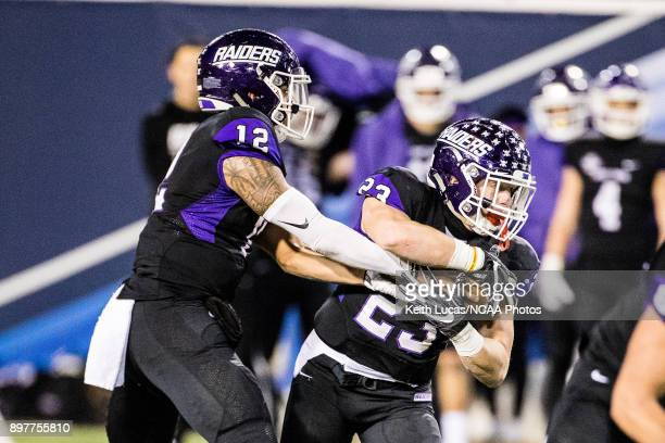 Angelo Fulford of the University of Mount Union hands the ball to Josh Petruccelli during the Division III Men's Football Championship held at Salem...
