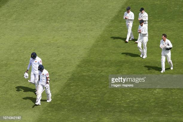 Angelo Mathews and Kusal Mendis of Sri Lanka are applauded by Kane Williamson Tom Latham Ross Taylor and BJ Watling of New Zealand as they leave the...