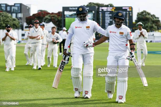 Angelo Mathews and Kusal Mendis of Sri Lanka are applauded by New Zealand players as they leave the field at the end of play on day four of the First...