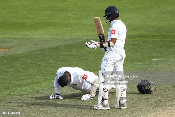 Angelo Mathews of Sri Lanka celebrates his century with a set of pushups while Kusal Mendis looks on during day four of the First Test match in the...