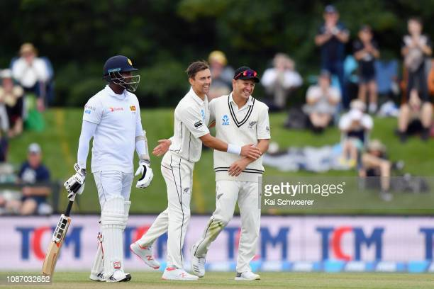 Angelo Mathews of Sri Lanka looks on as Trent Boult of New Zealand is congratulated by Neil Wagner of New Zealand after claiming his 6th and final...