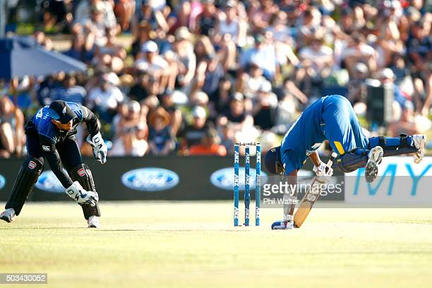 Angelo Mathews of Sri Lanka trips over as wicket keeper Luke Ronchi of New Zealand looks on during game five of the One Day International series...