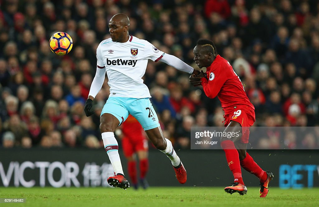 Angelo Ogbonna of West Ham United and Sadio Mane of Liverpool compete for the ball during the Premier League match between Liverpool and West Ham United at Anfield on December 11, 2016 in Liverpool, England.