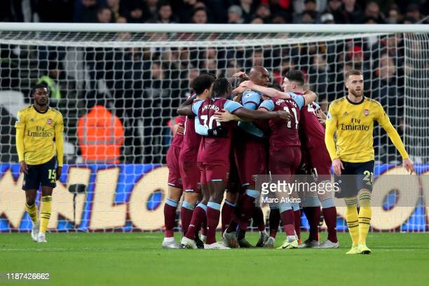 Angelo Ogbonna of West Ham United celebrates scoring the opening goal among team mates as dejected Arsenal player look on during the Premier League...