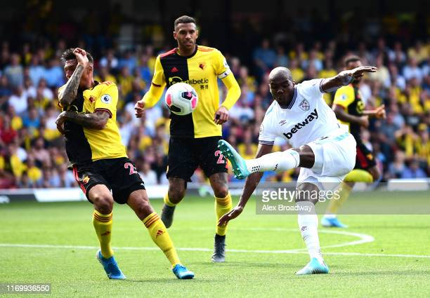 Angelo Ogbonna of West Ham United kicks the ball as Jose Holebas of Watford protects his face during the Premier League match between Watford FC and...