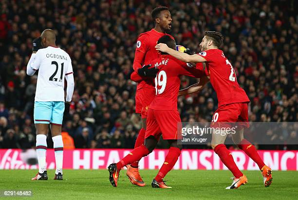 Angelo Ogbonna of West Ham United looks dejected as Divock Origi of Liverpool celebrates with Adam Lallana and Sadio Mane as he scores their second...