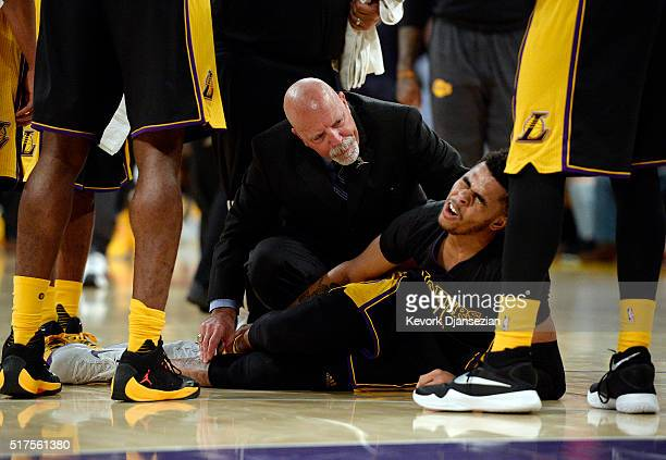 Angelo Russell of the Los Angeles Lakers grimaces in pain after injuring his right ankle as team athletic trainer Gary Vitti looks on during the...
