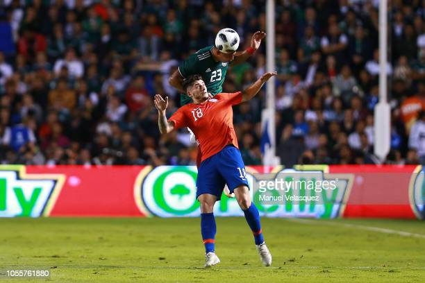Angelo Sagal of Chile struggles for the ball against Jesus Gallardo of Mexico during the international friendly match between Mexico and Chile at La...