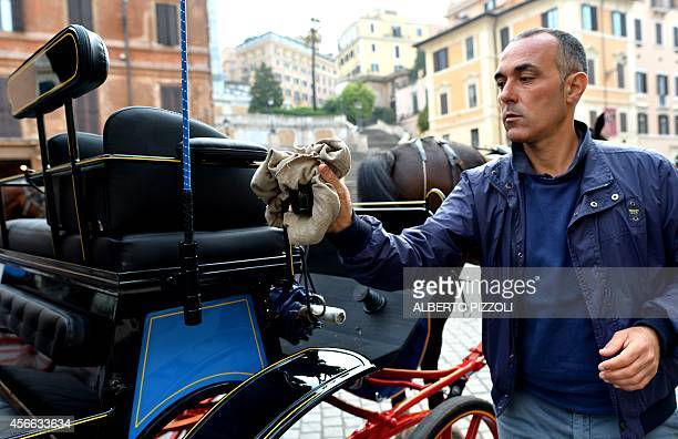 Angelo Sed president of the Romans horsedrawn carriage drivers cleans his carriage as he waits for clients at Piazza di Spagna on October 2 2014 in...