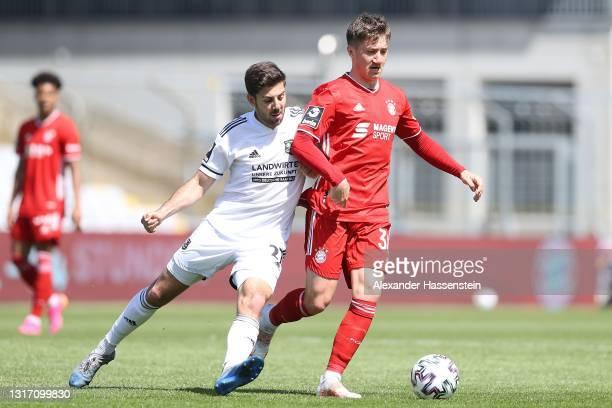 Angelo Stiller of Bayern München battles for the ball with Moritz Heinrich of Unterhaching during the 3. Liga match between Bayern München II and...