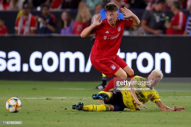 Angelo Stiller of Bayern Muenchen battles for the ball with Mesut Oezil of Arsenal London during the 2019 International Champions Cup match between...